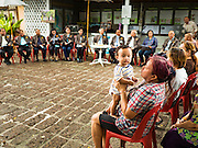 03 AUGUST 2016 - BANGKOK, THAILAND: Residents of the Pom Mahakan slum listen to members of the National Legislative Assembly's (NLA) housing extraordinary committee during a community meeting in the Pom Mahakan slum. Bangkok city officials officials told the residents of the slum that they must leave the fort and that their community will be torn down. The community is known for fireworks, fighting cocks and bird cages. Mahakan Fort was built in 1783 during the reign of Siamese King Rama I. It was one of 14 fortresses designed to protect Bangkok from foreign invaders. Only of two are remaining, the others have been torn down. A community developed in the fort when people started building houses and moving into it during the reign of King Rama V (1868-1910). The land was expropriated by Bangkok city government in 1992, but the people living in the fort refused to move. In 2004 courts ruled against the residents and said the city could take the land. Eviction notices have been posted in the community and people given until April 30 to leave, but most residents have refused to move. Residents think Bangkok city officials will start evictions around August 15, but there has not been any official word from the city.      PHOTO BY JACK KURTZ