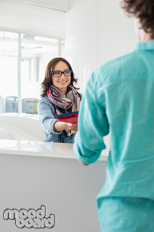 Smiling businesswoman handing over to male colleague at counter in creative office