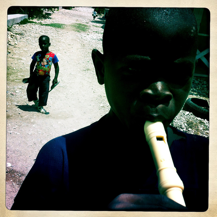 A boy plays the recorder at the Corail camp on Thursday, April 5, 2012 in Port-au-Prince, Haiti.