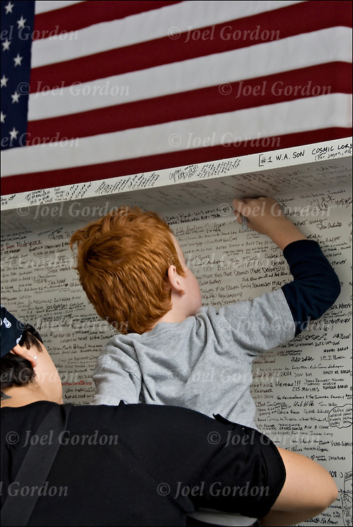 Mother holding up her young son who is adding his name to steel beam that will be used in the contruction of the National September 11 Memorial Museum on the 7th Anniversary of 9/11 at Battery Park in New York.