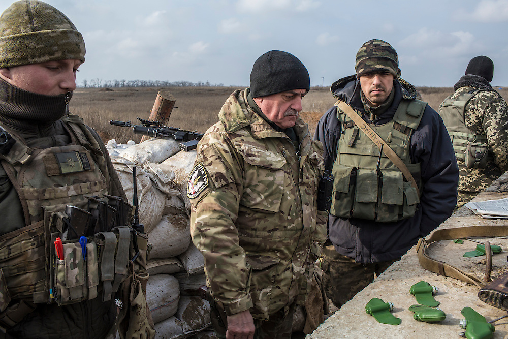 MARIINKA, UKRAINE - FEBRUARY 21, 2016: Lt. Col. Mikhailo M. Prokopiv, second from left, commander of Ukrainian Army forces in Mariinka, looks at non-functioning butterfly mines used for training purposes at a front-line position in Mariinka, Ukraine. The Donetsk suburb has been the scene of some of the heaviest fighting recently between Ukrainian forces and pro-Russian rebels. CREDIT: Brendan Hoffman for The New York Times