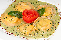 Plate of Ravioli de Aragosta, Pasta filled with fresh chunks of sweet lobster served in a lobster bisque sauce.