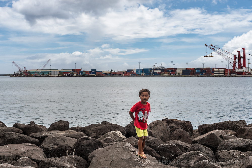 a child playing on his own on the breakwater in the port of Papeete.