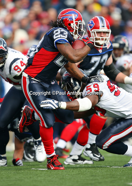 Buffalo Bills running back Marshawn Lynch (23) runs the ball while being tackled by Houston Texans linebacker DeMeco Ryans (59) during the NFL football game against the Houston Texans, November 1, 2009 in Orchard Park, New York. The Texans won the game 31-10. (©Paul Anthony Spinelli)