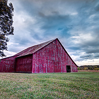 Red barn in a field with beautiful clouds and great detail - The story behind the shot at www.georgestrohlphotography.com