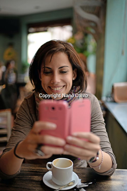 Attractive young woman using mobile phone in cafe