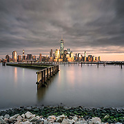 This photograph was taken during the first sunset of 2016.  While everyone else was recovering from their New Year's celebration, I was chasing the impressive cloud coverage and cozying up to my hand warmers by the wave breaker in Jersey City.  The sun was setting off to my right, which provide good light directly onto the buildings along the edge of the river on the Manhattan side.   This is one of my favorite vantage points in all of New York City and one that I have photographed extensively.  <br />
