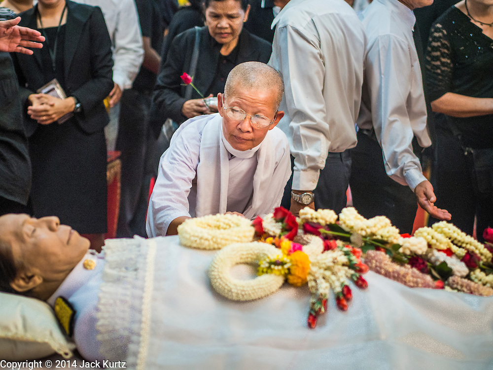 12 OCTOBER 2104 - BANG BUA THONG, NONTHABURI, THAILAND: A Buddhist nun pours scented water over the hand of Apiwan Wiriyachai on the first day of his funeral rites at Wat Bang Phai in Bang Bua Thong, a Bangkok suburb, Sunday. Apiwan was a prominent Red Shirt leader, member of the Pheu Thai Party of former Prime Minister Yingluck Shinawatra, and a member of the Thai parliament. The military government that deposed the elected government in May, 2014, charged Apiwan with Lese Majeste for allegedly insulting the Thai Monarchy. Rather than face the charges, Apiwan fled Thailand to the Philippines. He died of a lung infection in the Philippines on Oct. 6. The military government gave his family permission to bring him back to Thailand for the funeral. He will be cremated later in October. The first day of the funeral rites Sunday drew tens of thousands of Red Shirts and their supporters, in the first Red Shirt gathering since the coup.    PHOTO BY JACK KURTZ