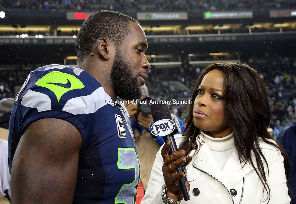 Seattle Seahawks strong safety Kam Chancellor (31) does a postgame television interview on the field with FOX Sports sideline reporter Pam Oliver after the NFL week 19 NFC Divisional Playoff football game against the Carolina Panthers on Saturday, Jan. 10, 2015 in Seattle. The Seahawks won the game 31-17. ©Paul Anthony Spinelli