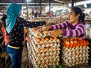 07 AUGUST 2017 - KECAMATAN, BALI, INDONESIA: A vender, right, sells eggs in the market in Kecamatan, in eastern Bali. Bali's local markets are open on an every three day rotating schedule because venders travel from town to town. Before modern refrigeration and convenience stores became common place on Bali, markets were thriving community gatherings. Fewer people shop at markets now as more and more consumers go to convenience stores and more families have refrigerators.     PHOTO BY JACK KURTZ