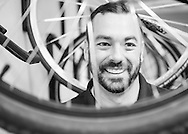 Instead of an office portrait, we wanted this headshot to reveal more of the client's personality.  Photography in the corporate bike room highlights the fact that this company promotes an active lifestyle.  Using the spokes of the bicycle wheel to frame the subject gives a more contemporary, fun layer to the portrait.  Turning the picture black and white hides the fact that we had to overcome horrible lighting conditions.