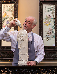 The Bonhams Asian Art Sale takes place on Thursday 15 November at 22 Queen Street Edinburgh starting at 11 am. It features Japanese and Chinese Art including: bronzes, jades, snuff bottles, porcelain, textiles, lacquer, paintings and furniture.<br /> <br /> Pictured: Danny McIlwraith of Bonhams holding a tall Blanc-De_Chine figure of Guanyin and Boy valued between £600 and £800