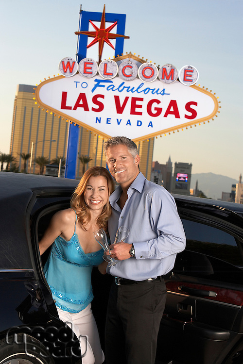 Couple getting out of limousine man holding empty glass in front of Welcome to Las Vegas sign