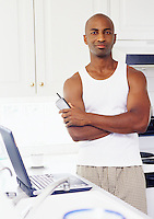 An African American man standing in his kitchen with cordless phone near his laptop computer.