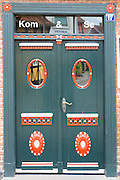 Painted front door of Kom and Se shop, corner Puggaardsgade and Sonderportsgade in Ribe centre, Denmark