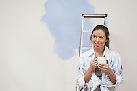 Woman having coffee by half-painted wall