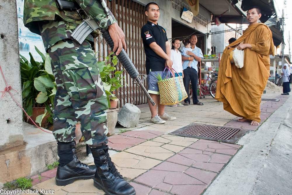 """Sept. 25, 2009 -- PATTANI, THAILAND: Soldiers and police officers accompany Buddhist monks on their morning rounds soliciting alms in Pattani, Thailand. Monks have been the targets of Muslim insurgent assassins who kill representatives of Thai Buddhist culture include monks and teachers. Thailand's three southern most provinces; Yala, Pattani and Narathiwat are often called """"restive"""" and a decades long Muslim insurgency has gained traction recently. Nearly 4,000 people have been killed since 2004. The three southern provinces are under emergency control and there are more than 60,000 Thai military, police and paramilitary militia forces trying to keep the peace battling insurgents who favor car bombs and assassination.  Photo by Jack Kurtz"""