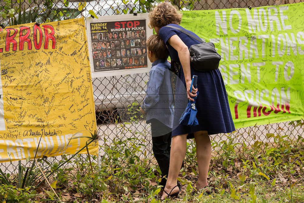 People stop to view a makeshift memorial wall on the spot where unarmed motorist Walter Scott was gunned down by police April 12, 2015 in North Charleston, South Carolina. About 100 people showed up for the brief vigil following a healing service at Charity Mission Baptist Church.