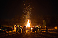 "Rathdrum High School students gather around a bonfire in a vacant lot between O'Malley's Sports Pub and the Country Nook restaurant in Rathdrum to get ""fired up"" for the school's Friday night football game against the Sandpoint Bulldogs."
