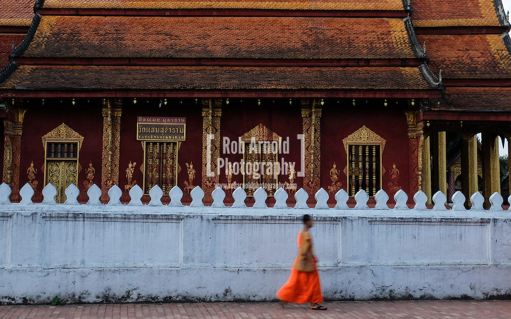 A novice walks past a temple in Luang Prabang