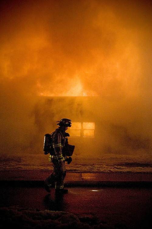 JEROME A. POLLOS/Press..A Coeur d'Alene firefighter walks down 12th Street south of Sherman Avenue as flames and smoke fill apartments that were destroyed Sunday.
