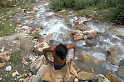 A labourer is having a bath near a little mountain spring along the Leh-Manali Highway.