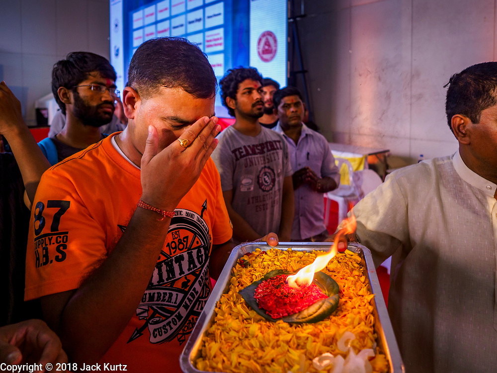 """23 SEPTEMBER 2018 - BANGKOK, THAILAND: A man makes an offering at the Ganesha Festival at Wat Dan in Bangkok. Ganesha Chaturthi also known as Vinayaka Chaturthi, is the Hindu festival celebrated on the day of the re-birth of Lord Ganesha, the son of Shiva and Parvati. The festival, also known as Ganeshotsav (""""festival of Ganesha"""") is observed in the Hindu calendar month of Bhaadrapada, starting on the the fourth day of the waxing moon. The festival lasts for 10 days, ending on the fourteenth day of the waxing moon. Outside India, it is celebrated widely in Nepal and by Hindus in the United States, Canada, Mauritius, Singapore, Thailand, Cambodia, and Burma.    PHOTO BY JACK KURTZ"""
