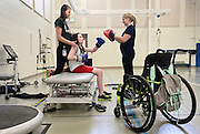 Riley Ljungdahl, 12, of Longmont, throws punches to Clinical Exercise Specialist Emma Dawson while steadied by CSU student and intern Julia De Jong during physical therapy, Tuesday, April 30, 2013, at the Peak Center at Craig Hospital.<br /> (Matthew Jonas/Times-Call)