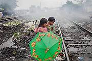 A girl is carrying her brother across the railway tracks passing through New Arif Nagar, one of the water-affected colonies near the abandoned Union Carbide (now DOW Chemical) industrial complex in Bhopal, Madhya Pradesh, India, site of the infamous 1984 gas tragedy. The poisonous cloud that enveloped Bhopal left everlasting consequences that today continue to consume people's lives.