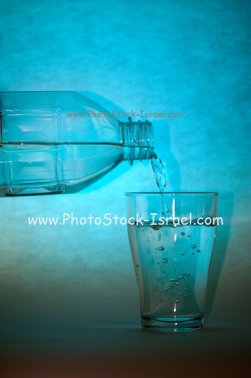 a glass and bottle of refreshing mineral water with ice cubes