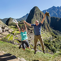 Peru, American backpackers leap to celebrate arrival at Machu Picchu with Huayna Picchu in background