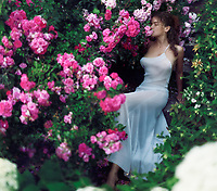 Romantic sensual portrait of a beautiful woman in a long elegant summer dress sitting on the stairs in a garden smelling the pink rose flowers