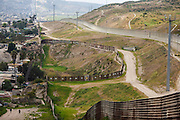 Two people walk by a dirt road beside the fence and border wall Mexico -U.S. The new border fence in the border between Mexico and US, has watchtowers and video cameras capable of recording at night, this makes the traffic in arms and drugs is more difficult, and even more for immigrants attempting to cross into the United States, in Tijuana, Mexico, on March 3, 2009.