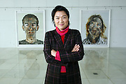 "Soho China Ltd. Co-CEO Zhang Xin poses in a gallery with photographs from a series called ""Survivor"" in Beijing, China, on February 16, 2006. ""Even artists who have never exhibited abroad are beginning to demand prices of 1 million yuan,"" said Zhang. ""These prices are unsustainable.""."