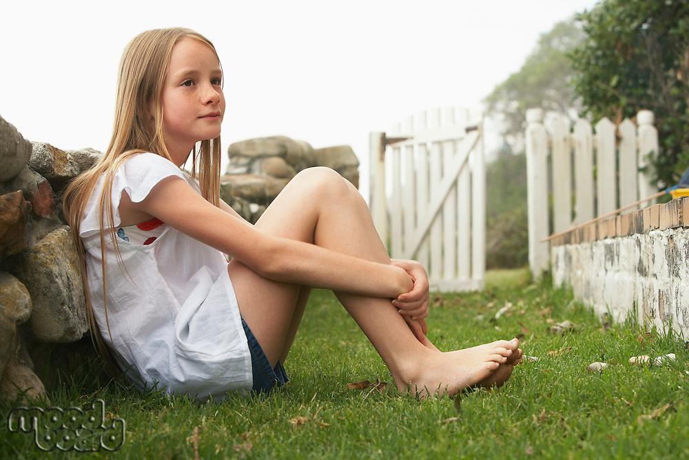 Girl (10-12) sitting against wall in garden