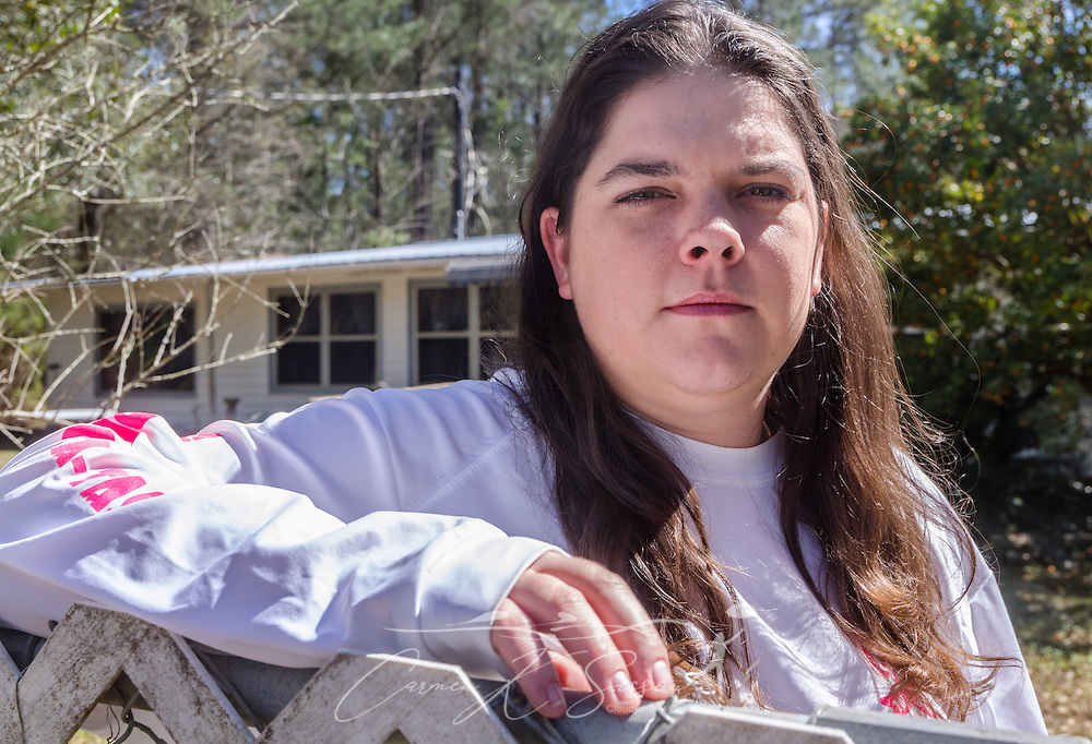 """Former day care worker Sara Morales is pictured in front of her home, March 4, 2016, in Loxley, Alabama. Morales worked briefly for day care owner Deborah Stokes at A Step Ahead Christian Day Care but says she quit because Stokes yelled at the children and failed to pay her. The day care, now closed, is one of several Stokes has opened over the past few years. Alleged problems and violations have brought the day cares under scrutiny, with critics saying that because the businesses operate as Christian day cares, they slip through a """"religious loophole"""" that allows them to bypass the licensing and safety standards required of non-Christian day cares. Stokes now operates another day care, Little Nemo's, in Spanish Fort, Alabama. (Photo by Carmen K. Sisson/Cloudybright)"""