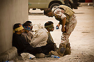 MOSUL, IRAQ - JUNE 05: An Iraqi soldier from 2nd Division gives water to detainees after returning to their base from a morning mission, on June 5 , 2010, in Mosul, Iraq. Iraq faces multiple challenges in the lead-up to the drawn-down of US forces in Iraq, with many observers claiming that while they have the capablities of handling home-grown problems, they are far from being able to tackle external threats. Political wrangling has reportedly fostered greater instability throughout the country with fears of renewed sectarian violence breaking out as insurgents set-up attacks in an attempt to exploit vulnerabilities amongst the populace. (Photo by Warrick Page)