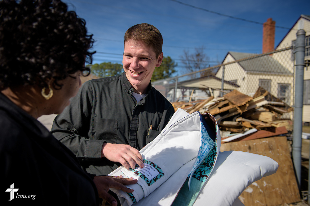 The Rev. Eric Hollar, associate pastor at Bethel Lutheran Church, Claremont, N.C., presents quilts to Bernice Cromartie, owner of Nanny's Korner Care Center, on Thursday, Jan. 19, 2017, in Lumberton, N.C. The center was damaged in October from flooding related to Hurricane Matthew. LCMS Communications/Erik M. Lunsford