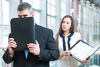 Businessman hides from coworker behind folder