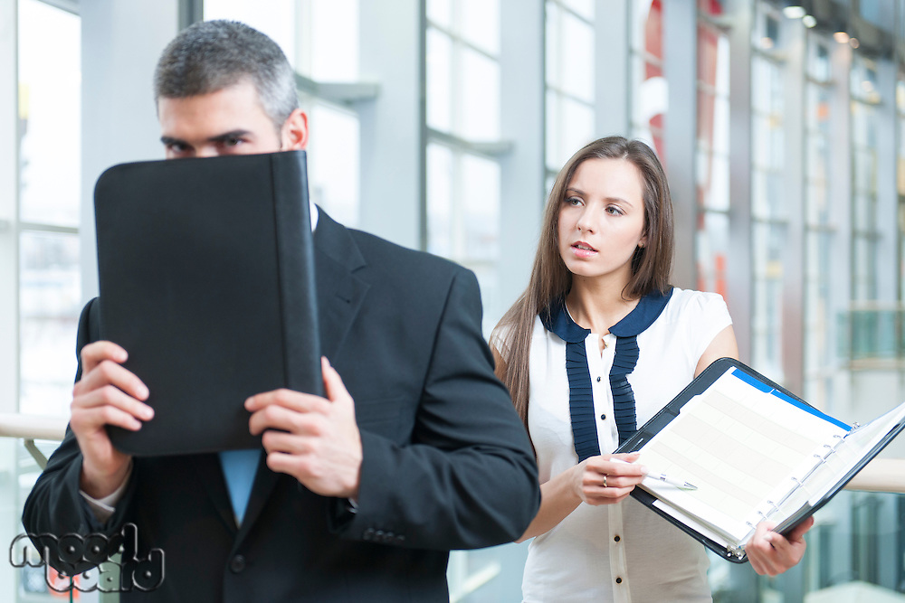 Businessman hides from coworker behind folder
