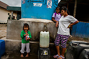 A mother and her child fill their jerry cans with water from water supply tank from government in Karo District,  North Sumatera Province, Indonesia  on July 10, 2015