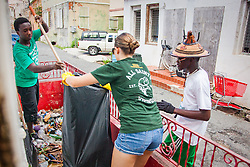 All Saints students clean up trash on the porch of a vacant residence.  Residents and volunteers gather for the Garden Street neighborhood cleanup and block Party hosted by E's Garden and Things, Long Path/Garden Street Community Association, and the Economic Development Authority's Enterprise and Commerical Zone Commission.  St. Thomas, USVI.  5 September 2015.  © Aisha-Zakiya Boyd