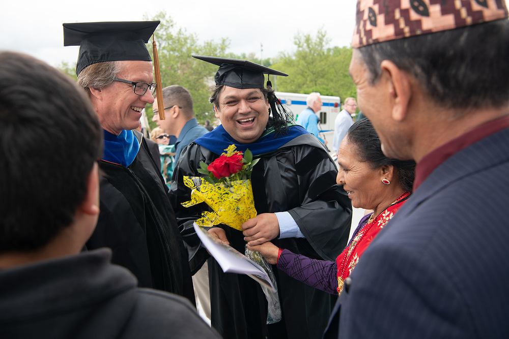 Rekam Giri (Center) introduces his Ph. D. adviser Carl Brune to his family following graduate commencement ceremonies. Photo by Ben Siegel