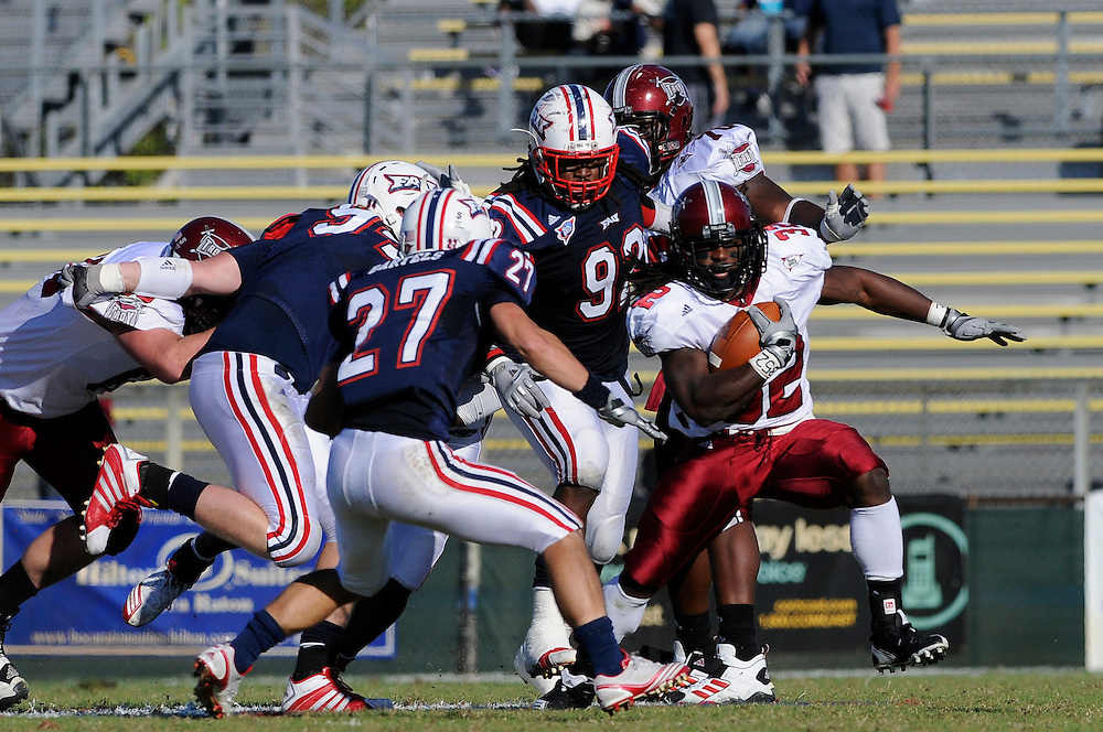 December 4, 2010: DuJuan Harris of the Troy Trojans rushes upfield as Kevin Cyrille (92), Andrew Stryffeler (94)and Marcus Bartels (27) give chase  during the NCAA football game between Troy and the FAU. The Trojans defeated the Owls 44-7.