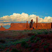 An almost velvet red cake sand color in the shadowed foreground provides a great contrast to the sunlit mesas and an incoming summer storm in Monument Valley