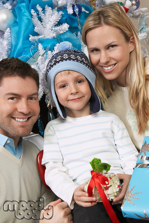 Couple with son (5-6) holding present in front of Christmas tree