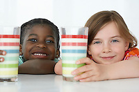 Two girls (5-6) leaning on table holding colourful glasses portrait close-up