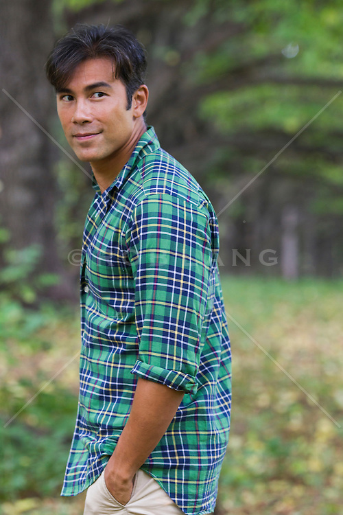 Asian American man enjoying a stroll in the woods by himself