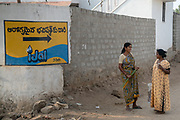 Local villagers stop to talk next to a signage displaying the iJal water station in Mecharajupalli village in Telangana, India.