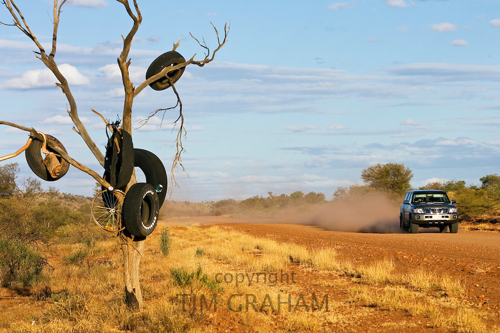 Tyres hang from a tree by the Mereenie Loop Road, Red Centre, Australia RESERVED USE - NOT FOR DOWNLOAD -  FOR USE CONTACT TIM GRAHAM